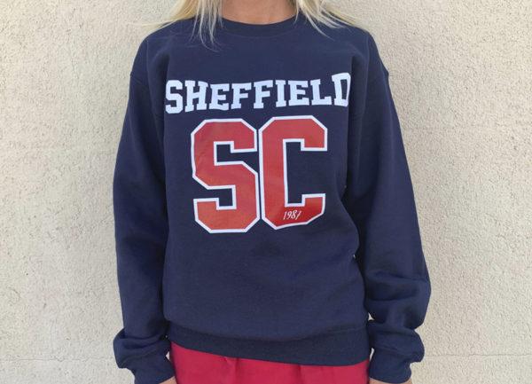 Sudadera azul con Sheffield en blanco y SC en color rojo con borde blanco.
